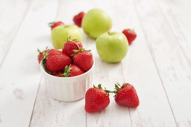 Detox concept. lekker fruit en bessen. gezond eten. veganisme, vegetarisme, rauwkostdieet. aardbeien en appels. zomer vers fruit. kopieer ruimte. vitaminen in voedsel. gezond ontbijt