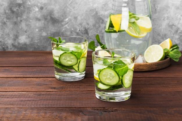 Detox drankje met komkommer, citroen en munt in glazen op een houten achtergrond. kopieer ruimte. voedsel achtergrond