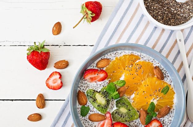 Detox en gezond superfoodsontbijt in kom. veganistische chiazaadpudding met amandelmelk met aardbeien, sinaasappel en kiwi. bovenaanzicht plat leggen