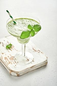 Detox groen groentesap of smoothie gegarneerd met blad van verse basilicum in cocktailglas op lichtgrijze leisteen, steen of betonnen ondergrond. bovenaanzicht met kopie ruimte.