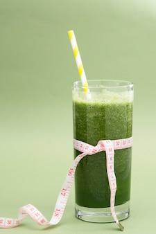 Detox groen smoothieglas voor los weegt, op dieet zijn, groene achtergrond. gezond eten.