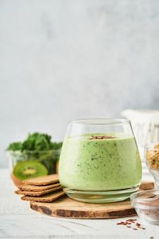 Detox groene smoothie met boerenkool, spinazie en kiwi op een lichtgrijze leisteen, steen of betonnen ondergrond. bovenaanzicht met kopie ruimte.