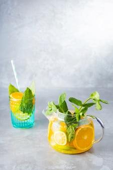 Detox limonadedrank van water, citroen, sinaasappel en muntblaadjes in een transparante theepot. lime mint ijsthee cocktail. zomers fris drankje. ruimte kopiëren