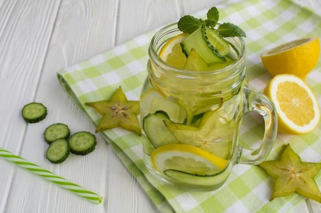 Detox of doordrenkt water met komkommer, carambola's en citroen op de witte houten achtergrond