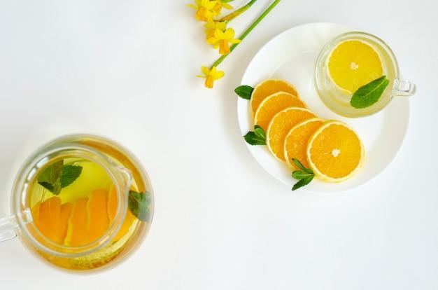 Detox thee in transparante theepot met oranje fruit en munt en gele narcissus bloem