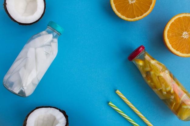 Detox water met kokos en sinaasappel in de glazen flessen op de blauwe achtergrond. bovenaanzicht. kopieer ruimte.