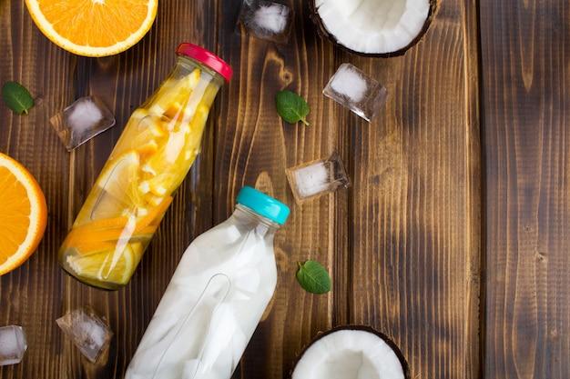 Detox water met kokos en sinaasappel in de glazen flessen op de bruine houten achtergrond. bovenaanzicht. kopieer ruimte.