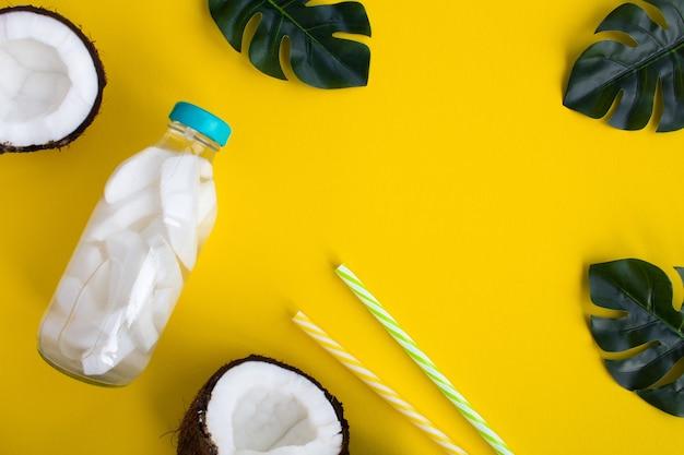 Detox water met kokos in de glazen fles op de gele achtergrond. bovenaanzicht. kopieer ruimte.