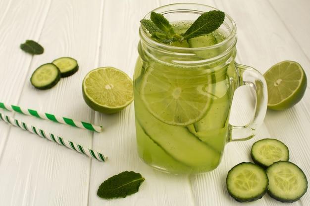 Detox water met komkommer en limoen op de witte houten achtergrond