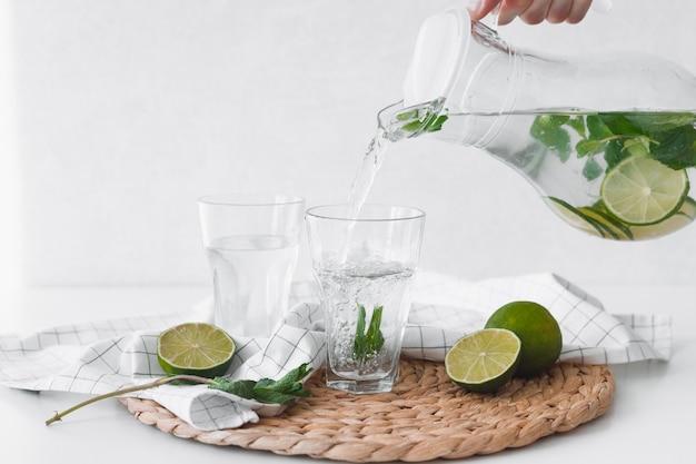 Detox water met limoenfruit. hand kalk fruit water uit kruik gieten in glazen.