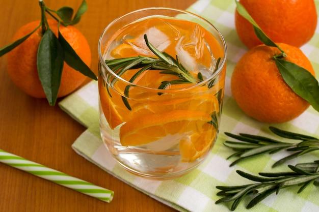Detox water met mandarijnen en rozemarijn op het groene servet