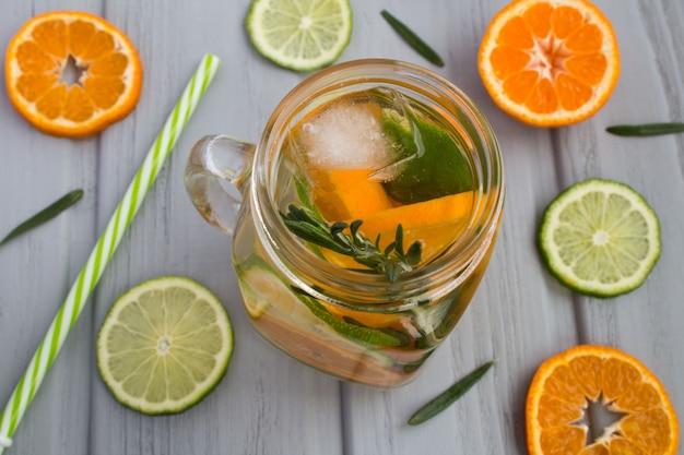 Detox water met mandarijnen, limoen en rozemarijn op de grijze houten achtergrond. van bovenaf bekijken.