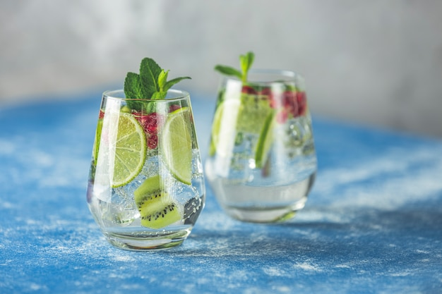 Detox water of martini tonic cocktail met kiwi, limoen en ijs, decoratie granaatappel en munt