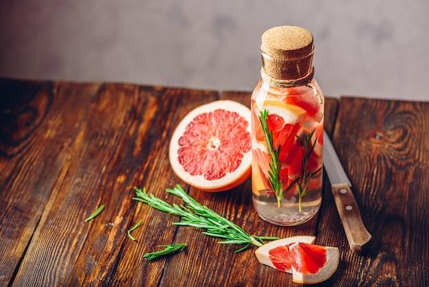 Detoxwater doordrenkt met gesneden grapefruit en verse bronnen van rozemarijn.