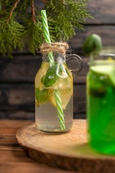 Detoxwater en vers sap in flessen met buizen op bruine houten achtergrond