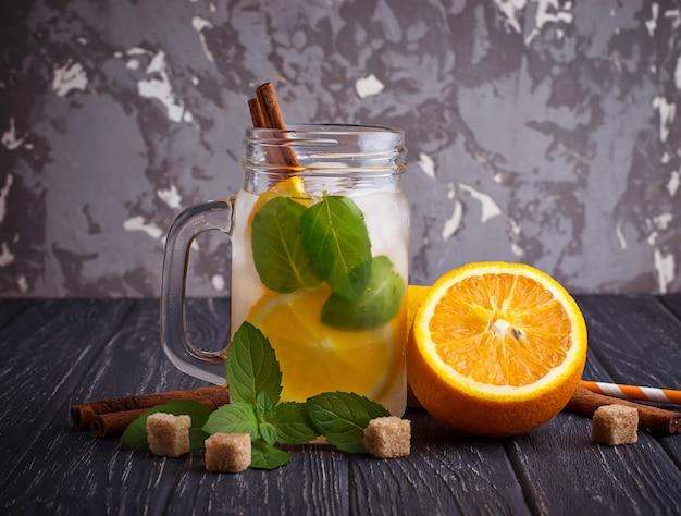 Detoxwater met sinaasappel, munt en kaneel in pot