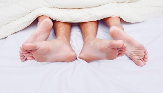 Deuken een paar voeten in bed. liefde, seks en partners.