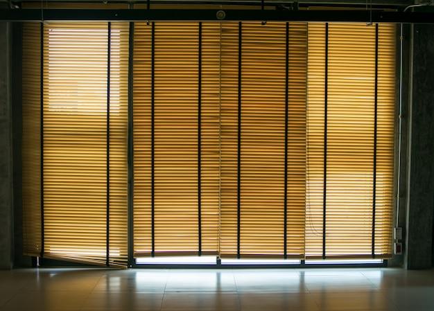 Deur en raam met metalen jaloezieën op zakelijke kamer