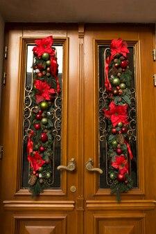 Deur versierd met dennentakken, bloemen en ballen. kerst decor