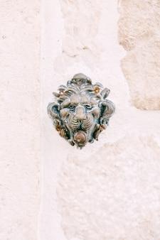 Deurbel snuit van een leeuw op een witte achtergrond in een stenen muur