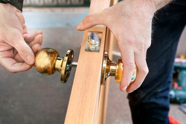 Deurinstallatie, arbeider installeert deurknop, houtbewerkerhanden.