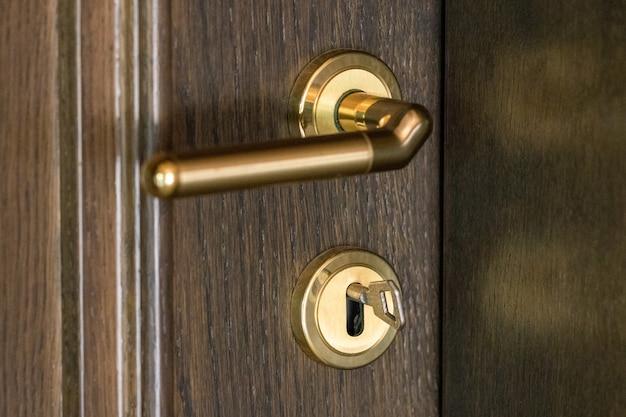 Deurklink. deurslot met sleutels. bruin houten deur close-up. nieuw huisconcept. onroerend goed.