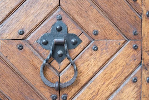 Deurklink van gesmeed metaal met een ring op een houten deur