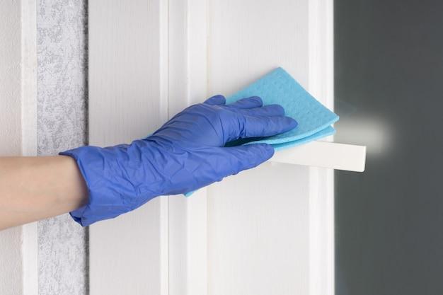 Deurklinken reinigen met een ontsmettingsmiddel tijdens een virale epidemie