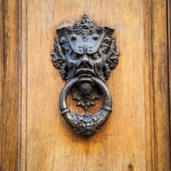 Deurklopper op een oude houten deur in toscane - italië