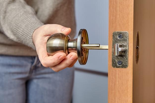 Deurknop in hand van timmerman tijdens installatie.