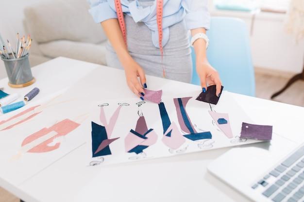Deze afbeelding beschrijft de processen van het ontwerpen van kleding in de werkplaats. er zijn handen van een meisje op zoek naar de schetsen en materialen op tafel.