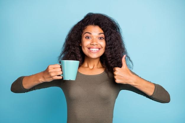 Deze cafetaria is geweldig! portret van positieve vrolijke donkere huid meisje houden kop hete cafeïne drank tonen duim-up feedback geven over uitstekende koffie dragen groene trui geïsoleerde blauwe kleur muur