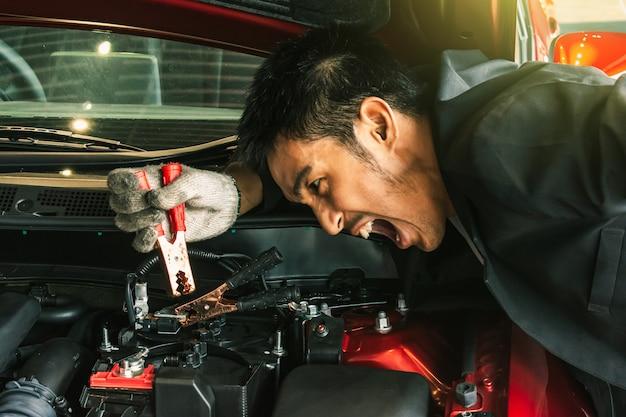 Deze carrière-inspectie aziatische man autoservice opladen van de batterij auto