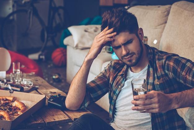Deze hoofdpijn doodt me! knappe jonge man die een glas water vasthoudt en er uitgeput uitziet