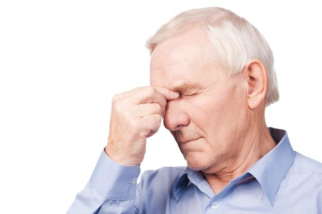 Deze pijn martelt me! gefrustreerde senior man in shirt die hand op zijn hoofd houdt en ogen gesloten houdt terwijl hij tegen een witte achtergrond staat