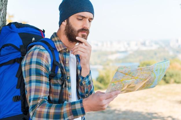 Deze plaats staat niet op de kaart. nadenkende jonge man die rugzak draagt en door een kaart kijkt
