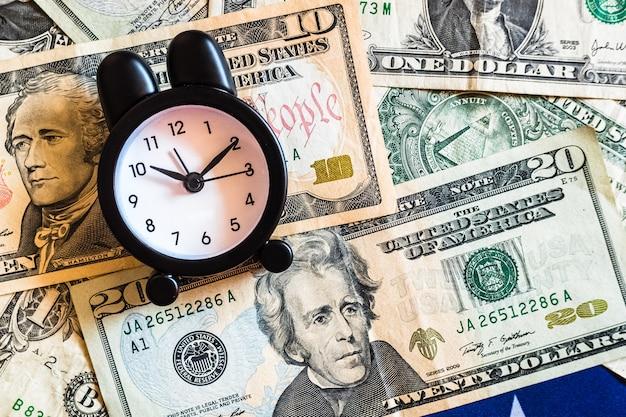Deze wekker met de woorden recessie op amerikaanse dollarbiljetten waarschuwt voor toekomstige crises.
