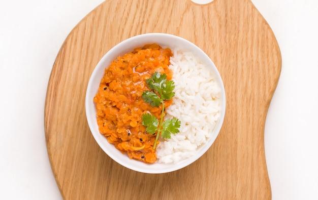 Dhal indiase linzensoep met rijst en kruiden in een witte kom op een houten bord