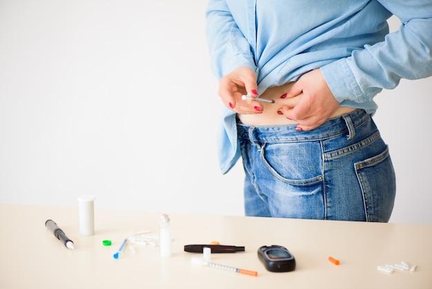 Diabetes patiënt insuline neergeschoten door spuit met dosis lantus, onderhuidse buikvaccinatie geïsoleerd op een witte achtergrond