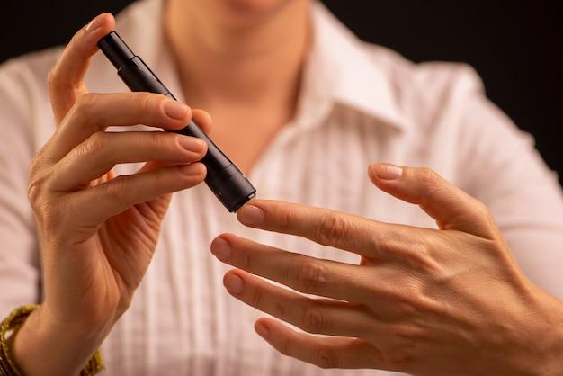 Diabetische patiënt die de bloedglucosespiegel controleert met behulp van een glucometer.