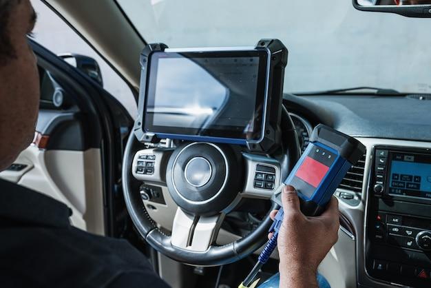 Diagnose van de auto. technische keuring, auto-elektronica. een latijnse man houdt een digitaliseringsapparaat vast.
