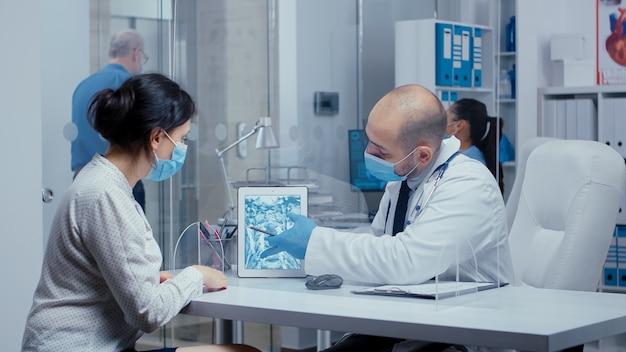Diagnose van de gezondheidszorg tijdens covid-19 voor vrouwelijke patiënt die door een plexiglaswand naar x ray kijkt op een digitale tablet. medisch consult in concept van beschermende uitrusting, shot van sars-cov-2 wereldwijd