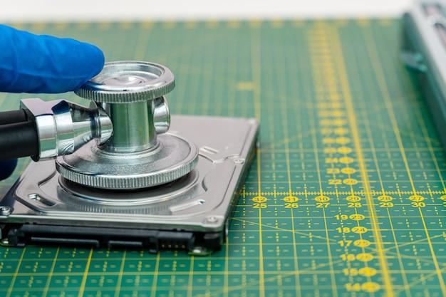 Diagnose van de harde schijf met een stethoscoop. herstel, zoek verloren gegevens, informatie in hdd-reparatieservice