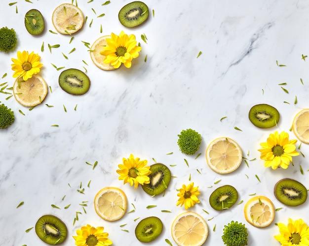 Diagonaal bloemenpatroon van lentebloemen, kiwi, schijfjes citroen. bloemenachtergrond met exemplaarruimte. bovenaanzicht
