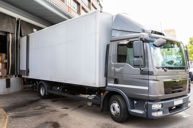 Diagonakmening van grijze vrachtwagen die voedingsmiddelen leveren in winkel