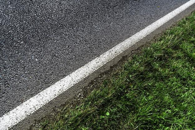 Diagonale foto van de witte grensstrook van de asfaltweg met groen grasmening