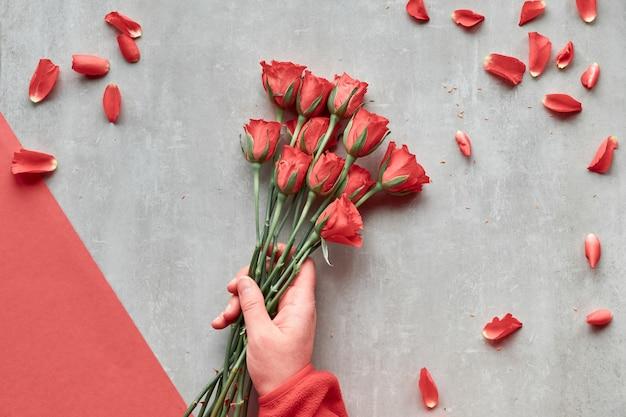 Diagonale geometrische papier achtergrond, kopie-ruimte. plat lag, vrouwelijke hand houdt rode rozen, verspreide bloembladen. bovenaanzicht, begroetingsconcept voor valentijnsdag, verjaardag, moederdag of een andere kleine gelegenheid.