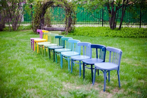 Diagonale rij kleurrijke houten stoelen op het gazon in de achtertuin die zich voorbereiden op een microhuwelijkscer...