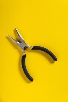 Diagonale tangen van dichtbij op gele achtergrond worden vaak gebruikt om elektriciteit te repareren.