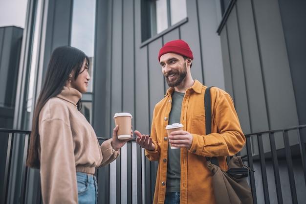 Dialoog. jonge man en vrouw in vrijetijdskleding die buiten praten